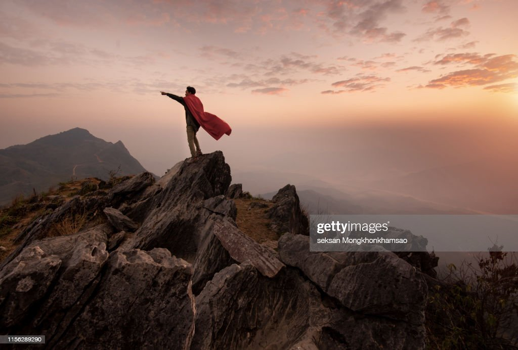 Businessman in a suit and cape hero on top of a mountain,Business Success concept. : Stock Photo
