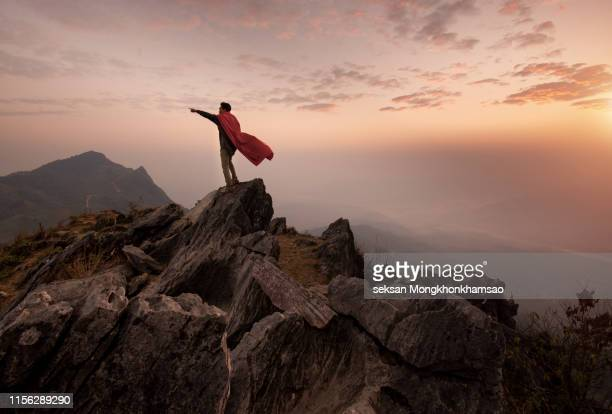 businessman in a suit and cape hero on top of a mountain,business success concept. - mondo beat foto e immagini stock