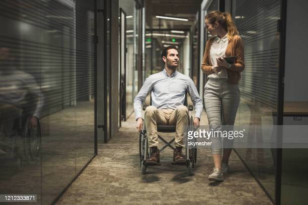 businessman in a wheelchair talking to his female colleague in at lobby. - wheelchair stock pictures, royalty-free photos & images