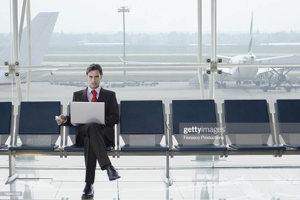 Businessman in airport with laptop and mobile phone : Stock Photo