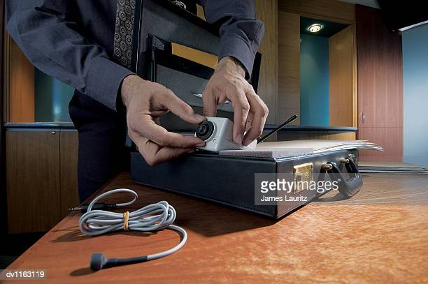 Businessman in An office Removing a Small Surveillance Camera From a Briefcase