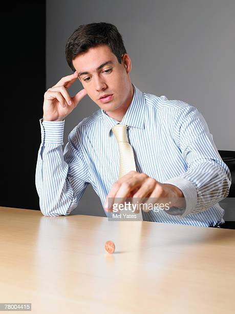 businessman in an office spinning a penny on a desk - penny for the guy stock photos and pictures