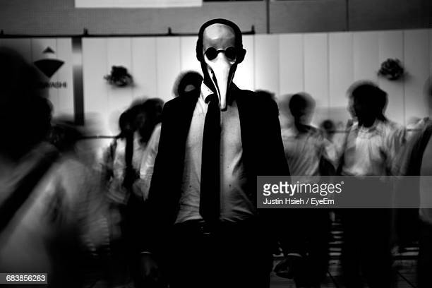Businessman In Animal Mask Against People In Office