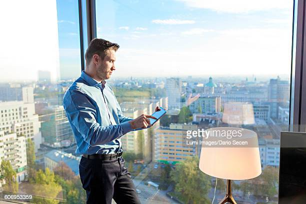 Businessman in apartment using digital tablet