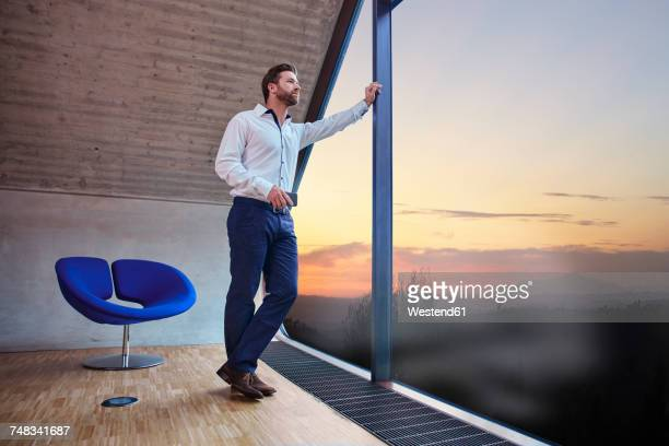 businessman in attic office looking out of window at sunset - man made space stock pictures, royalty-free photos & images