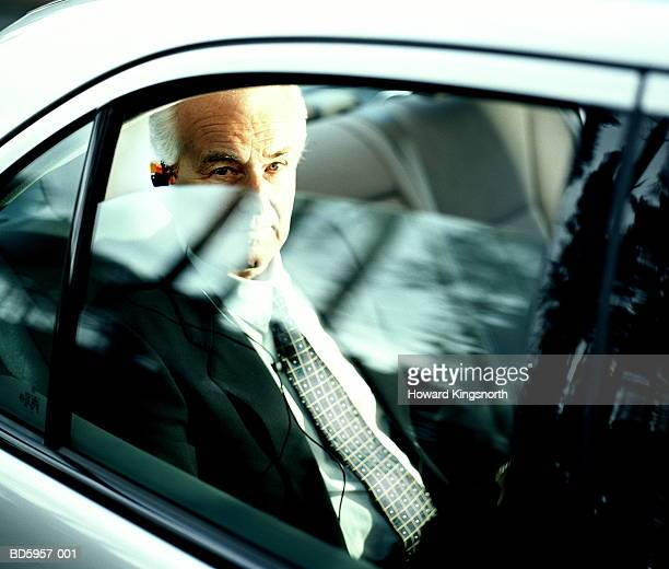 Businessman in back of car, view through window