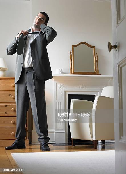 Businessman in bedroom removing tie, eyes closed, view through doorway