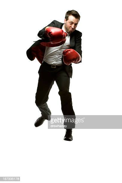 Businessman in black suit punching with red gloves