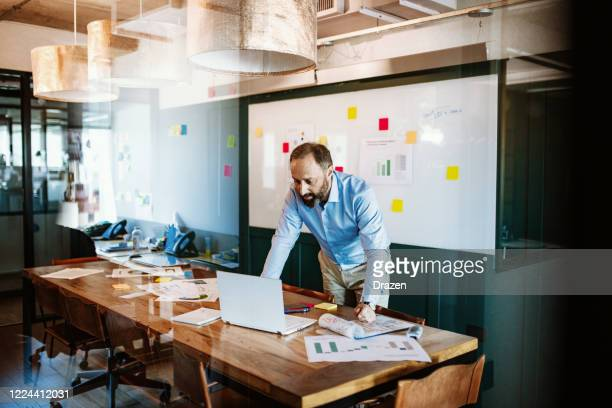 businessman in blue shit in board room - responsibility stock pictures, royalty-free photos & images