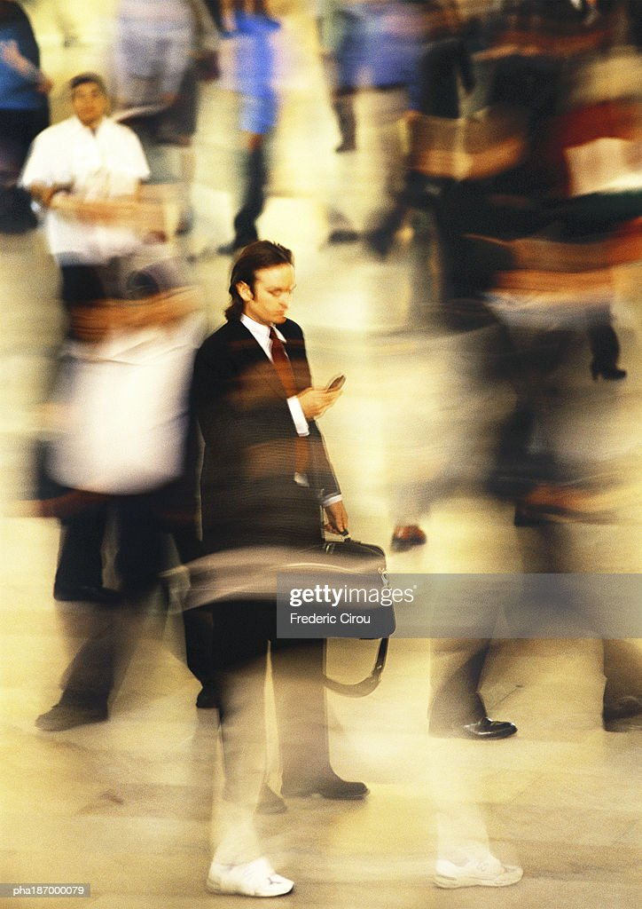 Businessman in blurred crowd, using cell phone, full length : Stockfoto