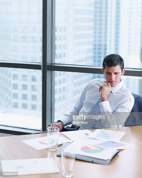 Businessman in boardroom with charts by large windows