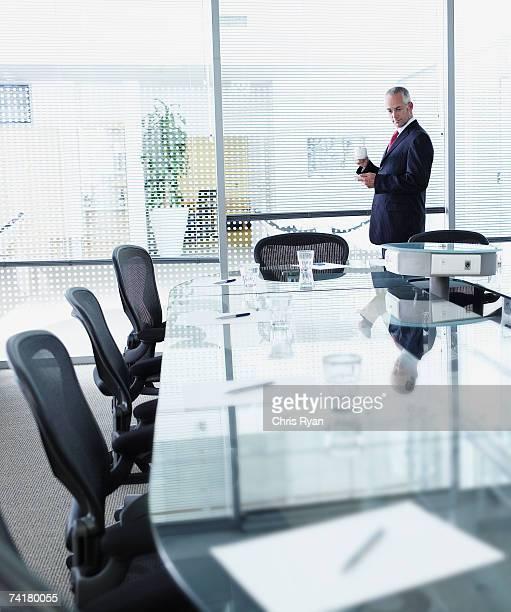 Empresário na sala de reuniões com grandes janelas