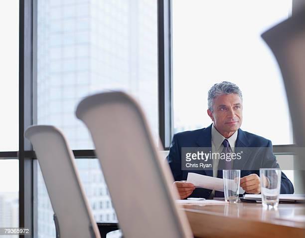 Geschäftsmann im Tagungsraum mit Papierkram