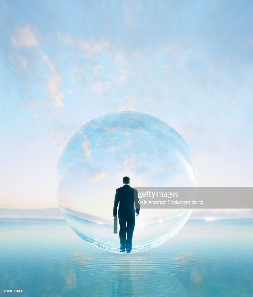 Businessman in bubble walking on water : Stock Photo