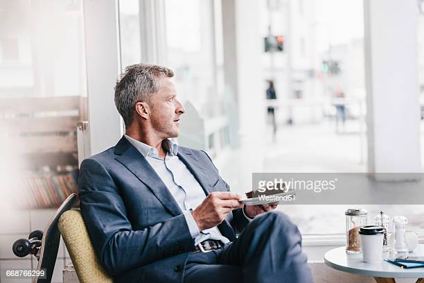 Businessman in cafe eating cake