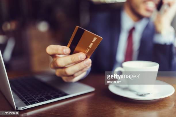 Businessman in cafe using credit card for online shopping