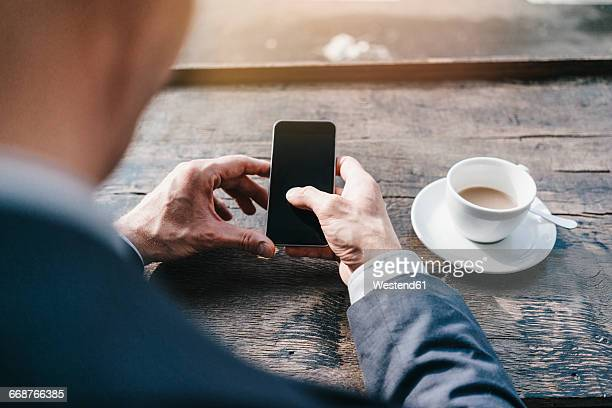 Businessman in cafe using smart phone