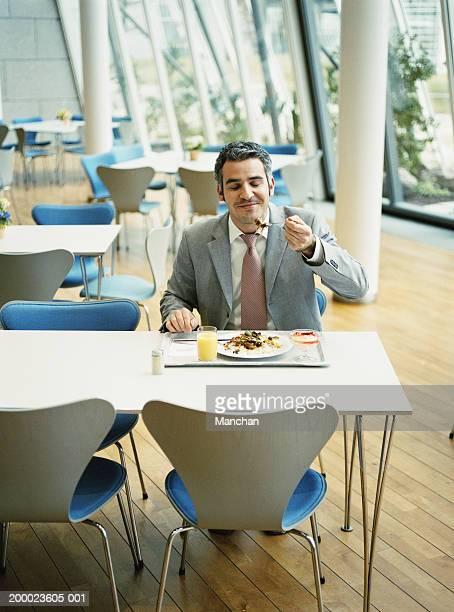 businessman in canteen eating lunch - ein mann allein stock-fotos und bilder