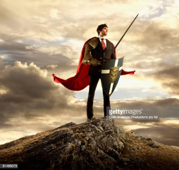 businessman in cape holding shield and sword - könig königliche persönlichkeit stock-fotos und bilder