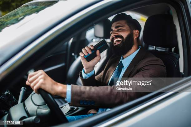 businessman in car - cantare foto e immagini stock