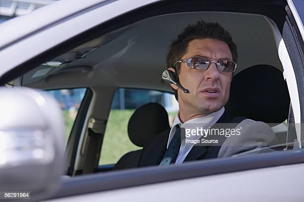 Businessman in car wearing headset
