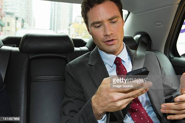 Businessman in car with smartphone