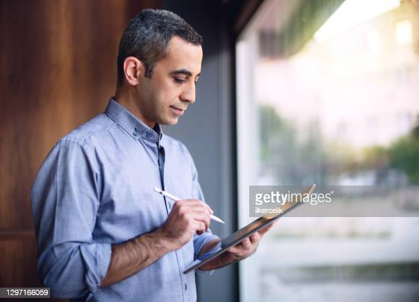 businessman in casual clothing writing on digital tablet using stylus nearby the window in the office - businesswear stock pictures, royalty-free photos & images