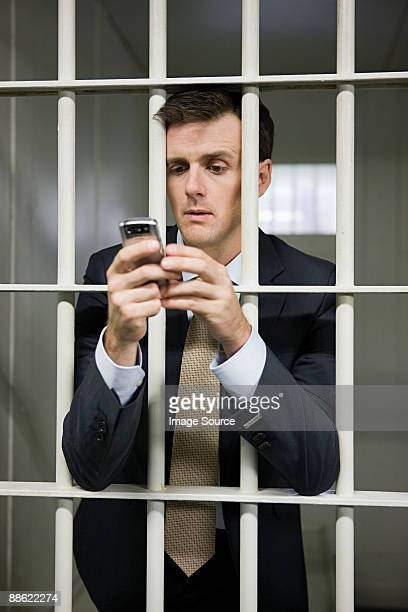 Businessman in cell with cellphone