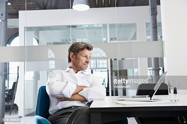 Businessman in conference room looking at laptop