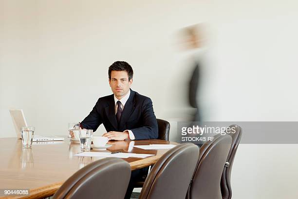 businessman in conference room with person in background passing by, munich, bavaria, germany - incidental people stock pictures, royalty-free photos & images