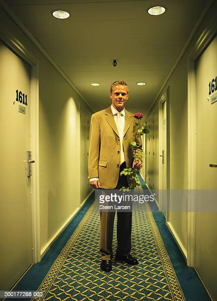 Businessman in corridor, holding red rose, smiling, portrait