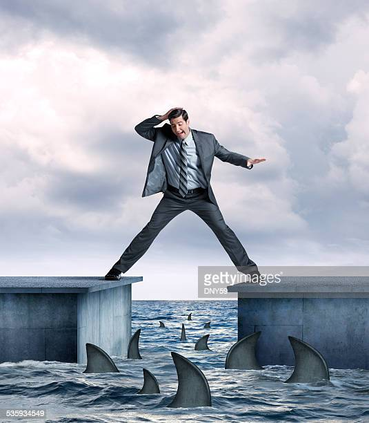 businessman in danger of falling into shark infested waters - shark fin stock photos and pictures