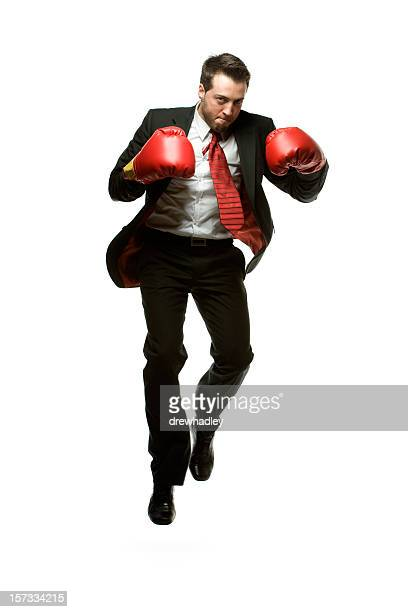 Businessman in dark suit jumping with red Boxing gloves.
