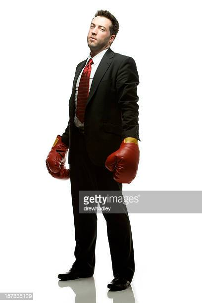 businessman in dark suit with red boxing gloves.. - fighting stance stock pictures, royalty-free photos & images