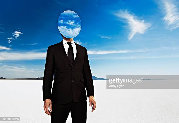 Businessman in desert with mirror head and clouds.
