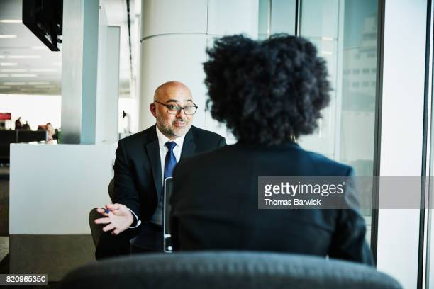 Businessman in discussion with colleague during meeting in airport while waiting for flight