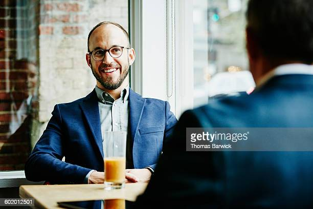 Businessman in discussion with colleagues in cafe