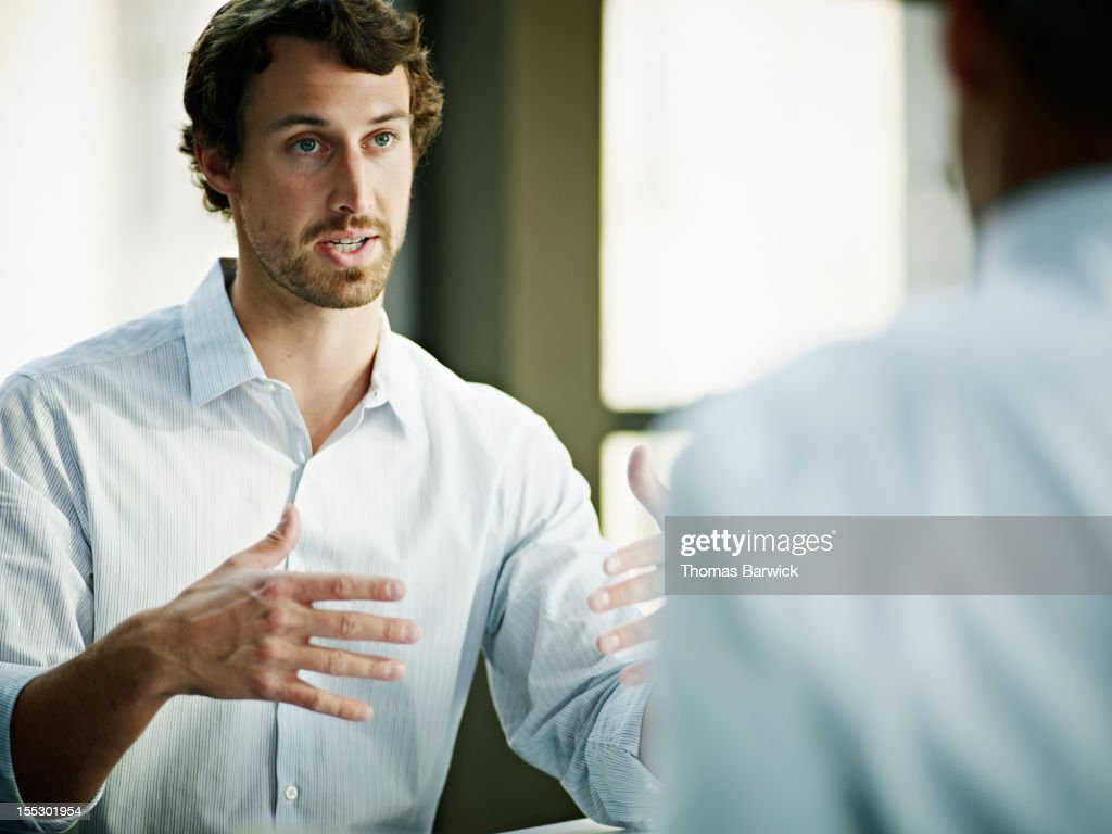 Businessman in discussion with coworker in office : Stock Photo