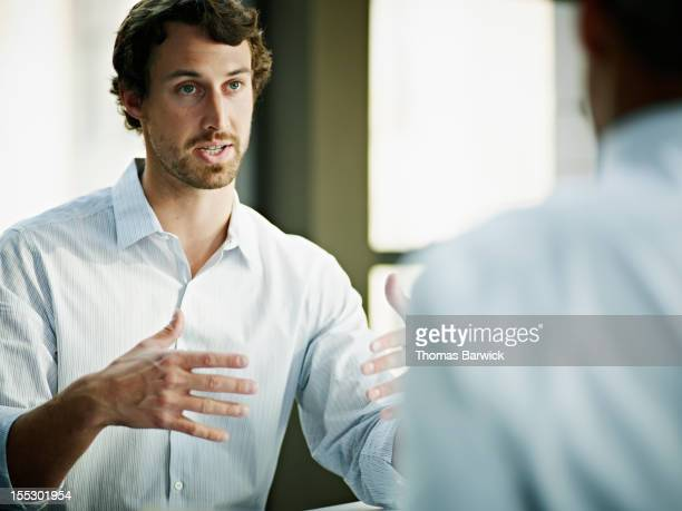 businessman in discussion with coworker in office - kommunikation themengebiet stock-fotos und bilder