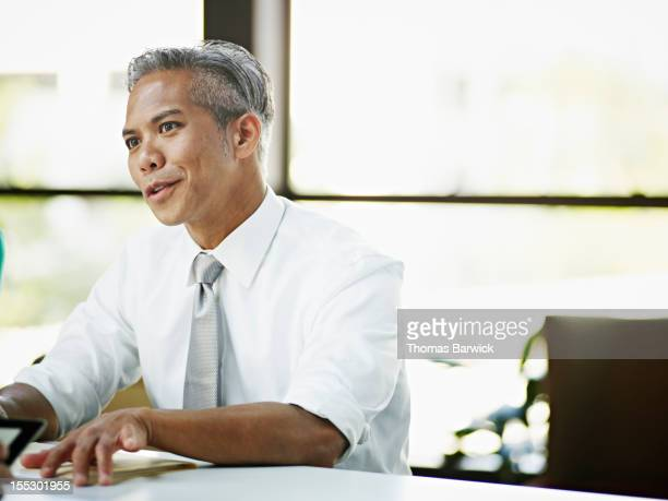 businessman in discussion with coworker in office - filipino ethnicity stock pictures, royalty-free photos & images
