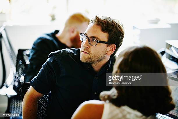 Businessman in discussion with coworkers in office