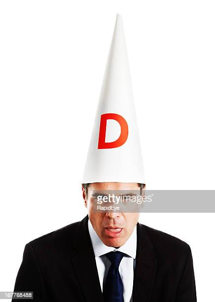Businessman in dunce cap looking really dumb