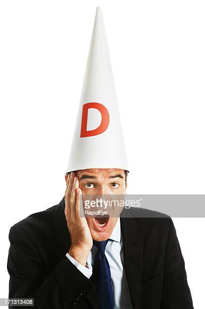 Businessman in dunce cap looking shocked with hand to face