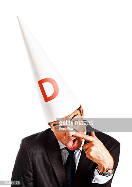 businessman in dunce cap makes stupid face: work is insane! - dunce's hat stock pictures, royalty-free photos & images