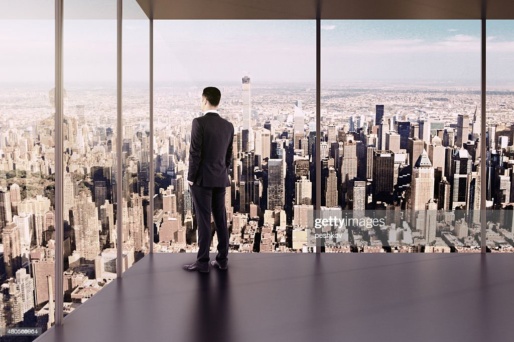 Businessman in empty office stands at the windows : Stock Photo