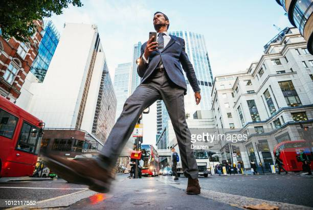 businessman in england crossing the street in the afternoon - wide angle stock pictures, royalty-free photos & images