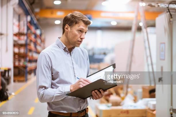 Businessman in factory holding folder