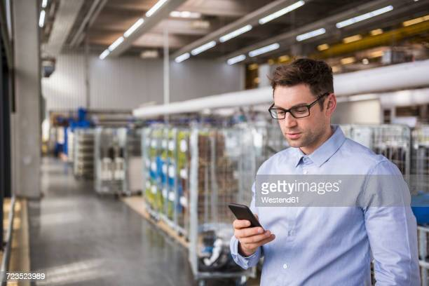 Businessman in factory shop floor looking at cell phone
