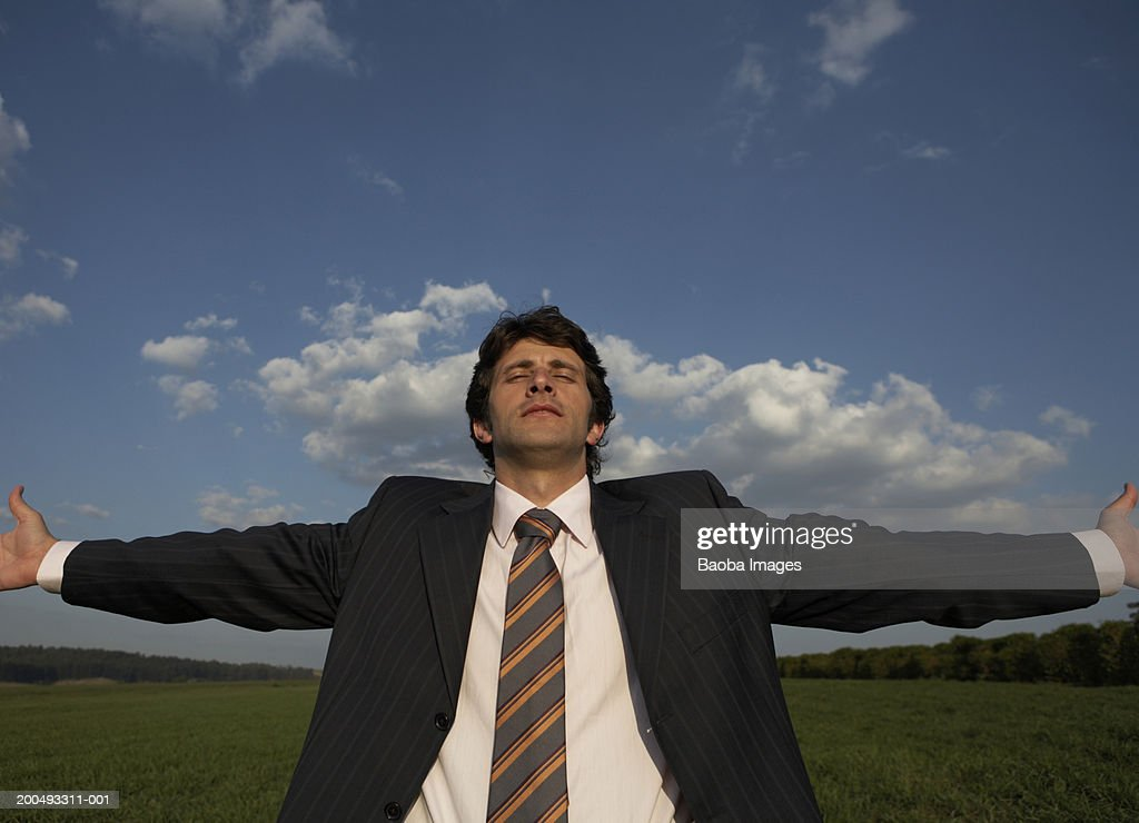 Businessman in field spreading arms wide : Stock Photo