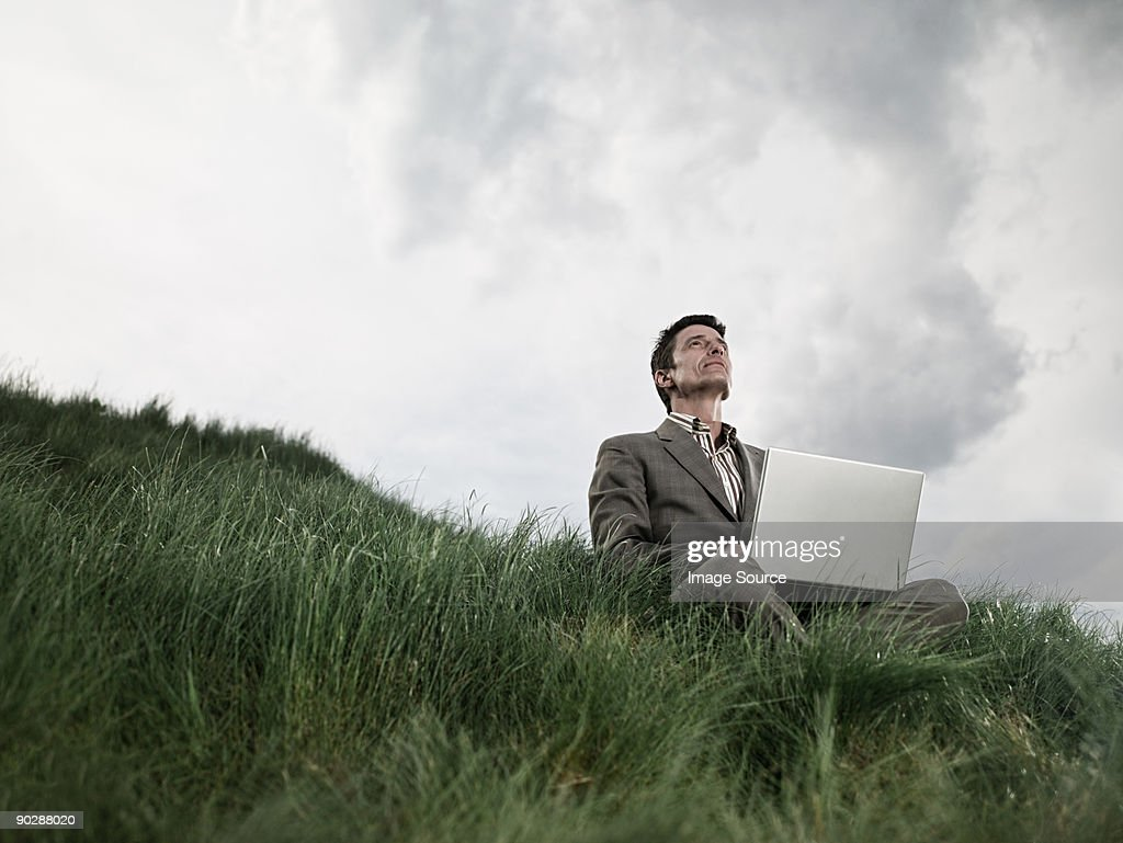 Businessman in field with laptop : Stock Photo
